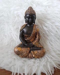 meditatie boeddha in de kleuren donker bruin en goud. keep van lotussen