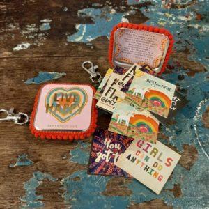 metalen doosje met live happy eriop in goud en een hartje in regenboog kleuren. met leuke vrolijke quote kaartjes erin