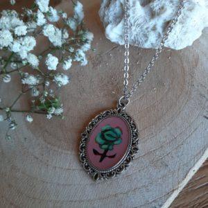 Een piepklein schilderijtje om je nek met groene roos en roze achtergrond