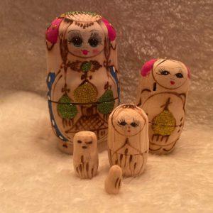 matroesjka glitter met 5 poppetjes hout. 2 gezichten erop geschilderd