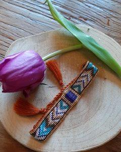 handgemaakt geweven armband van glaskralen brede band kleur wit met versieringen in de kleuren bruin blauw wit en goud met tassels