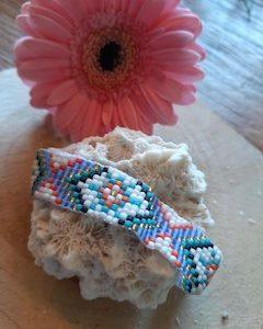 glaskralen geweven armband met klein bloemetje en kleuren blauw wit en roze