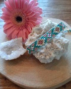 handgemaakt geweven armband van glaskralen brede band kleur wit met versieringen in de kleuren mint roze en wit en vleugjes goud