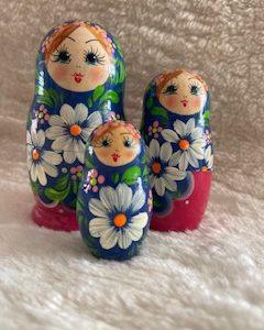 matroesjka met 3 verschillende poppetjes. blauw met roze. groene blaadjes en witte bloemetjes.