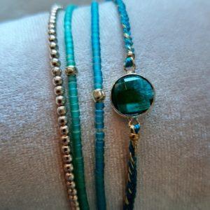set van 4 armbandjes in de kleuren turquoise blauw en goud. 1 met sblauwe steen
