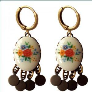 bronskleurige oorbellen met ovaal rondje in wit met daarop oranje en blauwe bloemen. met kleine vierkante rondjes aan de ooorbel
