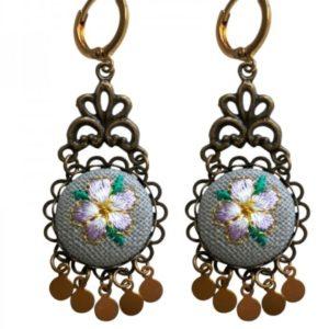 bronzige oorbellen met rond gehaakt ornament met daarop een paarse bloem met rinkelende rondjes aan de onderkant