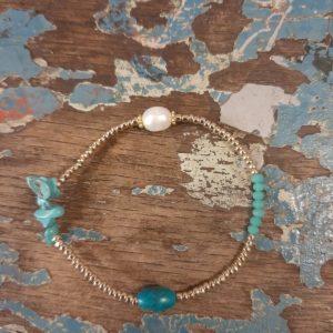elastieken armband met gouden kraaltjes en turqousie stenen. 1 parel