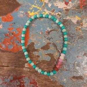 elastieken armbandje met turquoise steentjes en roze en donkerroze steentjes