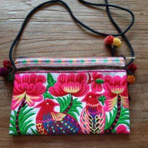 tasje met roze vogels en bloemen aan de uiteindes hangen pompons. ritssluiting aan de binnenkant