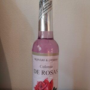 flesje met roze vloeistof en een etiket met een roos erop