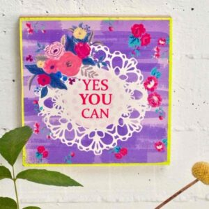 paarse walart met witte cirkel met tekst: yes you can omringd met bloemen. buitenkant goud geschilderd