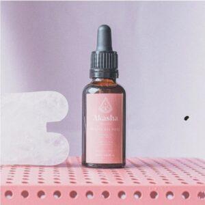 bruin flesje met pipet en een roze etiket met de tekst: facial oil rose