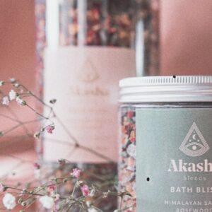 foto met 2 plastic doorzichtige potten met daarin de bathbliss met roze en bruine kleurtjes. etikes is grijs met daarop akasha en bath bliss