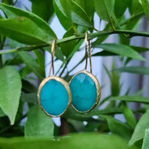 zee blauw kleurige steen met goudkleurige afwerking met haakje voor door het oor