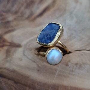 gouden ring met een vierkante blauwe steen en een ronde parel