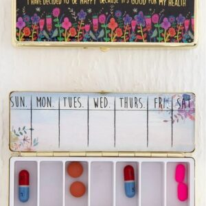 georganiseerde gouden pillen doos met vakjes van alle dagen van de week met daarop zwarte achtergrond en roze bloemen en teks today i decided to be happy