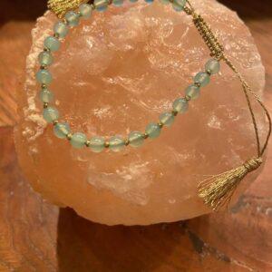 verstelabar armbandje gouden touwtje met tassels en aquamarijn steentjes eraan