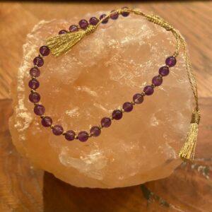 armbandje met gouden touwtjes en tassels aan de uiteinde. amethist steentjes paars
