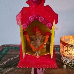 houten rode altaart met geel en roze en een witte ganesha in de altaar
