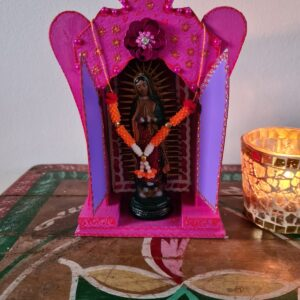 kleurrijk houten altaartje van hout met de virgin of guadelupe met gouden en oranje afwerkingen. hoofdkleur roze en paars