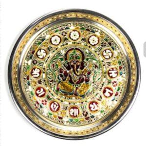 indiaase schaal met in het midden ganeshe met daarom heen allerlei versiering in goud groen en rood