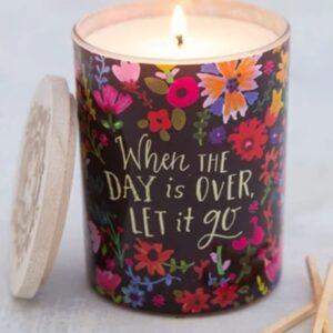 zwarte achtergrond met kleurige bloemen op een glazen pot bedrukt met de tekst: when the day is over let it go. met daarin een geurkaars geur mango