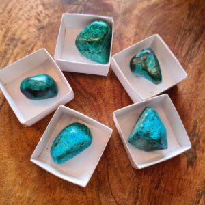 5 groenze stenen in een klein wit doosje.