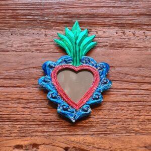 roze hartje met daarin een spiegeltje de buitekant ervan is blauw met bovenop groene versiering in de vorm van een vlammetje