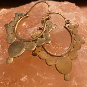 gouden oorbelle rond met in het midden een groot gouden platte circel met aan de rest van de oorbellen kleine cirkels