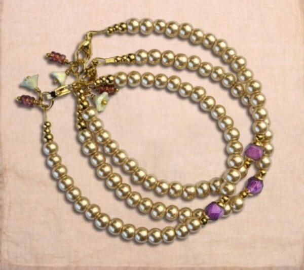 armband met allemaal pareltjes en in het midden een amethist steen slotje is goudkleurig