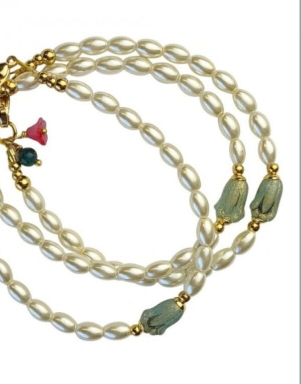 ivoorwitte parels en aquablauw bloemetje van ruw glas. Bij het slotje zijn twee kleine elementjes bevestigd: een kersenrood glazen bloemetje en een kraal van groene jaspis.