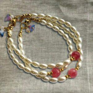 armband met ovale pareltjes en een roze steen in het midden, slotje en kraaltjes naast de steen zijn van goud