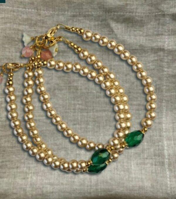 crèmekleurige parels en een facetgeslepen smaragdgroene kraal. Bij het slotje zijn twee kleine elementjes bevestigd: een bleekgroen glazen bloemetje en een kraal van cherry quartz.