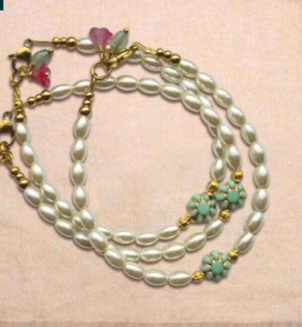 ivoorwitte parels en oud mintgroen glazen bloemtje met gouden details. Bij het slotje zijn twee kleine elementjes bevestigd: een kersenrood glazen bloemetje en een kraal van Aventurijn.