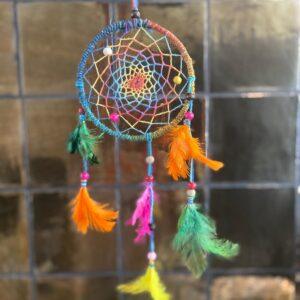 mooie regenboog dromenvanger met alle kleurtjes van de regenboog. verwerkt met kraaltjes in het gehaakte middenstuk en fel gekleurde veertjes aan de onderkant