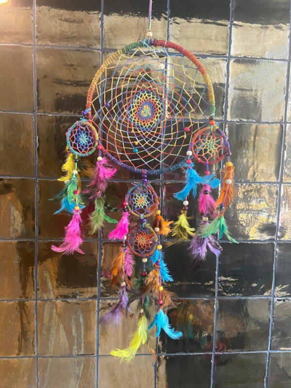 super mooie regenboogdromenvanger in alle kleuren van de regenboog. gehaakt mideen stuk met daarin kralen. onderaan gekleurde veren en ook kralen