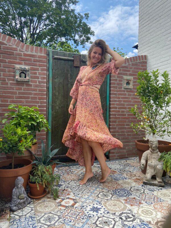 super mooie lange jurk met riuffles en een open rug en cut outs aan de zijkant. in de leur roze met groen en een vleugje rood